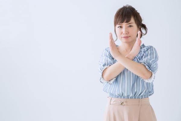 バツ印のジェスチャーをしている女性