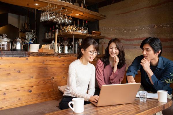 カフェでPCを触る男女三人の画像